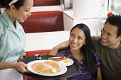 Asian couple being served food at diner