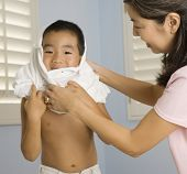 Asian mother helping son put on shirt