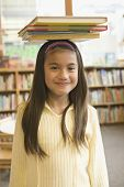 image of pacific islander ethnicity  - Pacific Islander girl balancing library books on head - JPG