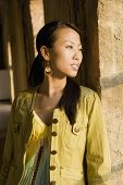 Asian woman leaning on column