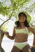 Hispanic girl in bathing suit under tree