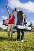 Hispanic couple carrying camping supplies