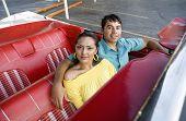 Hispanic couple sitting in convertible