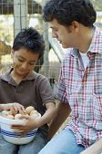 Multi-ethnic father and son with bowl of eggs