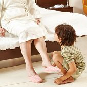 Child helping senior woman at home in bedroom to put on slippers