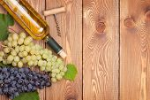 White wine bottle and bunch of grapes on wooden table background with copy space