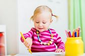 Adorable happy toddler girl drawing with coloring pencils, perfect for early education context