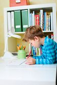 Cute happy schoolkid at home drawing or studying