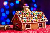 Gingerbread house decorated with colorful candies over Christmas tree lights background