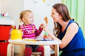 picture of babysitter  - Young mother and her toddler girl playing together with finger toys - JPG