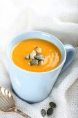 Cup Of Pumpkin Soup On Knitted Woolen Fabric