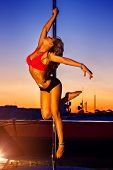 Young sexy pole dance woman on urban background.