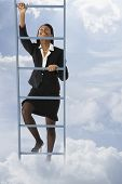 African businesswoman climbing ladder in clouds
