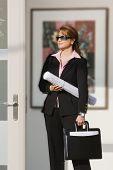 Asian businesswoman holding blueprints