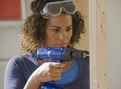 African woman using cordless drill
