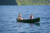 Asian mother and daughter rowing in canoe