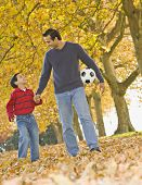 Hispanic father and son with soccer ball in park