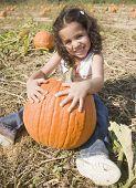 Hispanic girl sitting with pumpkin