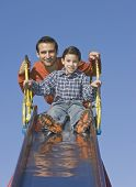 Hispanic father and son at top of slide