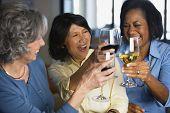 Multi-ethnic women toasting with wine
