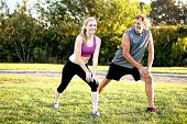 Happy young couple exercising together in a park