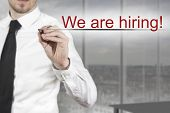 Businessman Writing We Are Hiring In The Air