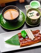 Premium Quality Grilled Eel, Miso Soup And Sake Served In Japanese Restaurant. Asian Food Background