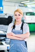 Female auto mechanic working in car workshop