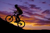 foto of exercise bike  - a silhouette of a man riding a mountain bike up a hill - JPG