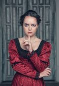 Beautiful Medieval Woman In Red Dress Making Silence Gesture