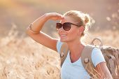 Portrait of cute happy traveler girl in dry ripe wheat field, looking away and enjoying beautiful ag