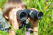 Boy hiding in grass looking through binoculars outdoor