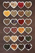 Large herb tea selection in heart shaped porcelain bowls over lokta paper background with titles