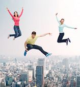 happiness, freedom, friendship, movement and people concept - group of smiling teenagers jumping in air over city background