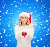 happiness, winter holidays, christmas and people concept - smiling young woman in santa helper hat with red heart decoration over blue snowy background