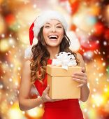 christmas, xmas, new year, happiness concept - laughing asian woman in santa helper hat with gift box