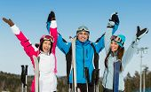 Half-length portrait of group of alps skier friends with hands up. Concept of cute winter sport and funny vacations with friends