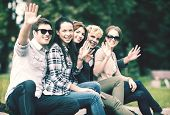 summer holidays, education, campus and teenage concept - group of students or teenagers waving hands