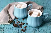 Cups of coffee with marshmallow and napkin on wooden table