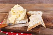 Fresh homemade butter on paper and sliced bread, on cutting board, on wooden background