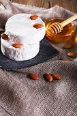 Camembert cheese on plate, honey in glass bowl and nuts on sackcloth background