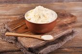 Fresh homemade butter in bowl, on wooden background