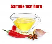 Homemade natural infused olive oil in glass sauce-boat with red chili peppers, garlic isolated on white
