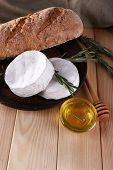 Camembert cheese on plate, bread, honey in glass bowl and napkin on wooden background
