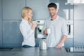 image of early 20s  - Attractive couple enjoying their early morning coffee standing together in the kitchen chatting with their mugs in their hands - JPG