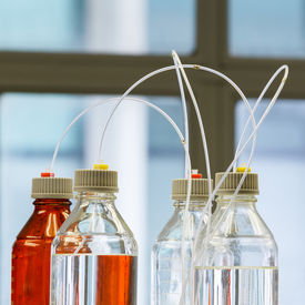 picture of hplc  - Close up clear and amber color bottle with plastic hose for High performance liquid chromatography  - JPG