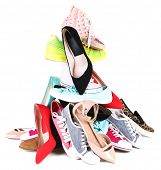Pile of various female shoes isolated on white