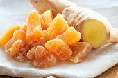 stock photo of home remedy  - Closeup dried candied crystallized ginger pieces and fresh rhizome root on rustic table - JPG