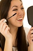 Cute Ethnic Teen Applying Her Mascara Holding A Mirror Laughing