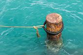 Rusty Mooring Bollard With Ship Ropes